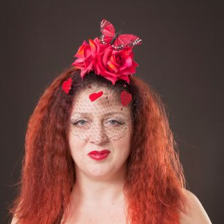 THe Headonista is wearing a red rose, butterfly and heart fascinator